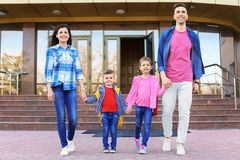 Happy young parents taking their little children to school. Young parents taking their little children to school stock photography