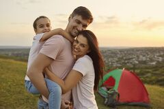 Free Happy Young Parents With Child Hugging At Their Camp In Mountains. Girl With Mom And Dad Embracing On Camping Trip Royalty Free Stock Images - 187024189