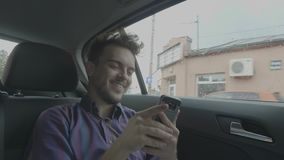 Happy young passenger man taking selfie photos with his smartphone and posting on Facebook while traveling by uber taxi car -. Happy young passenger man taking stock footage