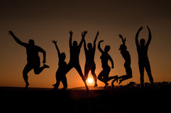 Happy young people. Group of happy young people silhouettes jumping on the beach Stock Images