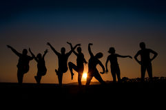 Happy young people. Group of happy young people silhouettes dancing on the beach Royalty Free Stock Photos