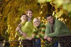Happy young people in autumn park. Happy young people standing in autumn park, leaning to railing Stock Photo
