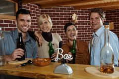 Happy young people in bar. Happy young people standing at bar in pub, drinking beer, looking at camera, smiling Stock Images