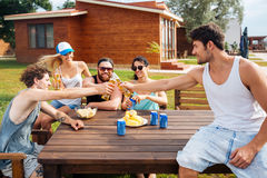 Happy young people with beer celebrating at the table outdoors Royalty Free Stock Photography