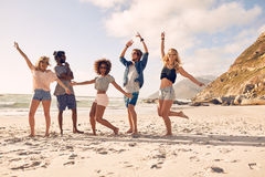 Happy young people dancing on the beach. Multi-ethnic group of friends together on the beach having fun. Happy young people dancing on the beach. Group of Royalty Free Stock Photography