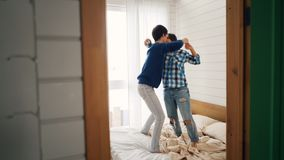 Happy young people are dancing on bed at home moving bodies and holding hands enjoying love and leisure time together