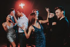 Happy Young People Dancing on New Year Party. Happy New Year. People Have Fun. Indoor Party. Celebrating of New Year. Young Woman in Dress. Young Man in Suit royalty free stock images