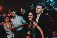 Happy Young People Dancing on New Year Party. Happy New Year. People Have Fun. Indoor Party. Celebrating of New Year. Young Woman in Dress. Young Man in Suit stock photo