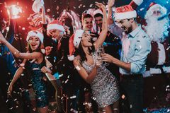 Happy Young People Dancing on New Year Party. Santa Claus. People in Red Caps. Happy New Year Concept. Glass of Champagne. Celebrating of New Year. Young Woman stock photos