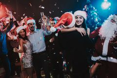 Happy Young People Dancing on New Year Party. Happy New Year. People Have Fun. Indoor Party. Celebrating of New Year. Young Woman in Dress. Young Man in Suit royalty free stock photo