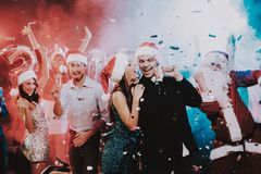 Happy Young People Dancing on New Year Party. Happy New Year. People Have Fun. Indoor Party. Celebrating of New Year. Young Woman in Dress. Young Man in Suit stock photos