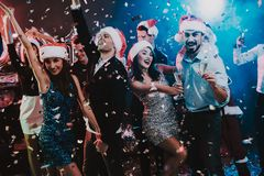 Happy Young People Dancing on New Year Party. Santa Claus. People in Red Caps. Happy New Year Concept. Glass of Champagne. Celebrating of New Year. Young Woman royalty free stock photography