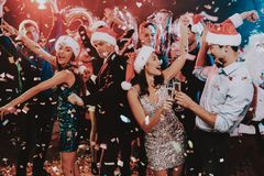 Happy Young People Dancing on New Year Party. Santa Claus. People in Red Caps. Happy New Year Concept. Glass of Champagne. Celebrating of New Year. Young Woman royalty free stock images