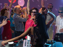 Happy young people dancing in night club. Happy, young people flirting and dancing on the dancefloor, in a night club dj mixing Royalty Free Stock Images