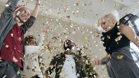 Happy young people are dancing throwing gold confetti at celebration party. Beautiful girls and guys are celebrating the. New Year or Christmas, they are stock footage
