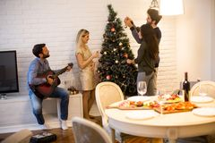 Young people decorate fir-tree for holidays of Christmas and New Stock Photos