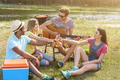 Happy young people drinking alcohol in nature. Lets drink for us. Cheerful young friends are celebrating event near river. They are clinking glasses and smiling Stock Images