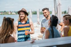 Happy young people drinking beverages and spending time together. At beach bar stock photography
