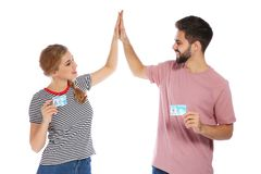 Happy young people with driving licenses on white. Background royalty free stock image