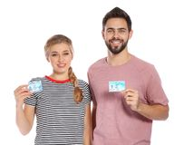 Happy young people with driving licenses. On white background stock image