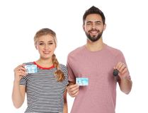 Happy young people with driving licenses. On white background royalty free stock photography