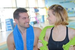 Happy young people flirting in pool area Stock Photography