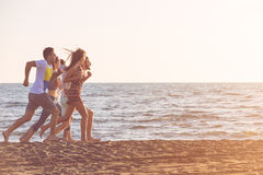 Happy young people group have fun white running and jumping on beach at sunset time.  Royalty Free Stock Photo