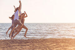 Happy young people group have fun white running and jumping on beach at sunset time.  Stock Photography