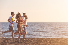 Happy young people group have fun white running and jumping on beach at sunset time.  Stock Photo
