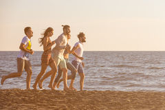 Happy young people group have fun white running and jumping on beach at sunset time.  Royalty Free Stock Image