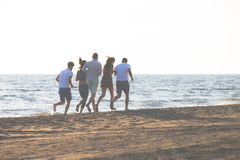 Happy young people group have fun white running and jumping on beach at sunset time.  Stock Photos