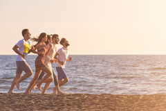 Happy young people group have fun white running and jumping on beach at sunset time Royalty Free Stock Photo