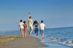 Happy young people group have fun white running and jumping on beacz at sunset time Stock Photos