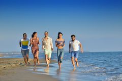 Happy young people group have fun white running and jumping on beacz at sunset time Royalty Free Stock Photography
