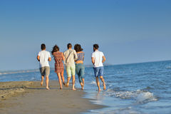 Happy young people group have fun white running and jumping on beacz at sunset time Stock Image