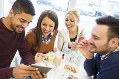 Happy young people having fun in a cafe,eating cake Stock Image