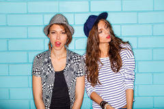 Happy young people having fun in front of blue brick wall. Lifestyle portrait of two beautiful best friends hipster girls wearing stylish bright outfits, denim Royalty Free Stock Images