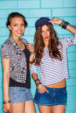 Happy young people having fun in front of blue brick wall. Lifestyle portrait of two beautiful best friends hipster girls wearing stylish bright outfits, denim Stock Photo