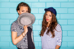 Happy young people having fun in front of blue brick wall. Lifestyle portrait of two beautiful best friends hipster lady wearing stylish bright outfits, denim Stock Photos