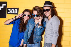 Happy young people having fun in front of yellow brick wall. Lifestyle portrait of beautiful adult hipsters wearing stylish bright outfits and sunglasses and Stock Image