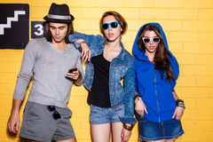 Happy young people having fun in front of yellow brick wall. Lifestyle portrait of beautiful best friend hipsters wearing stylish bright outfits and sunglasses Stock Images