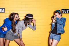 Happy young people having fun in front of yellow brick wall. Lifestyle portrait of beautiful best friend hipsters wearing stylish bright outfits and sunglasses Royalty Free Stock Images