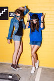 Happy young people having fun in front of yellow brick wall. Lifestyle portrait of two beautiful best friends hipster girls wearing stylish bright outfits, denim Royalty Free Stock Image