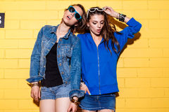 Happy young people having fun in front of yellow brick wall. Lifestyle portrait of two beautiful best friends hipster girls wearing stylish bright outfits, denim Stock Image