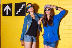 Happy young people having fun in front of yellow brick wall. Lifestyle portrait of two beautiful best friends hipster women wearing stylish bright outfits, denim Royalty Free Stock Photography