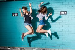 Happy young people having fun and jumping in front of blue brick stock images