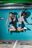 Happy young people having fun and jumping in front of blue brick Stock Photos