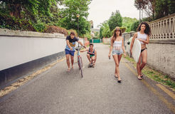 Happy young people having fun with skateboard and bicycle Royalty Free Stock Photos