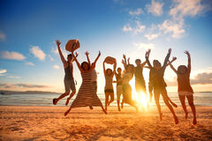 Happy young people jumping at the beach on beautiful sunset stock photos