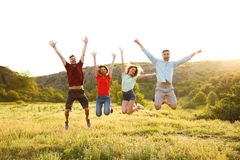 Happy young people jumping in wilderness. Camping season stock image